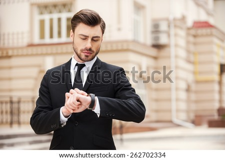 I will be in time. Handsome young man in formalwear looking at his watch while standing at the street  - stock photo