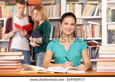 I will be ready to my final exam. Confident young woman sitting at the library desk and smiling while two people reading a book on the background