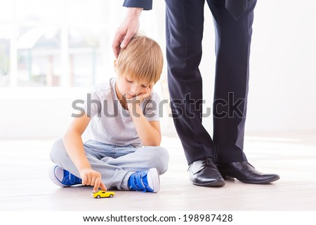 I will come back soon. Sad little boy leaning his face on hand while playing with toy car and looking down while his father in formalwear consoling him  - stock photo
