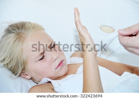 I will not to take medicine - little sick girl in bed - stock photo