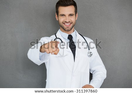 I will take care of your health! Cheerful young doctor in white uniform pointing at camera while standing against grey background - stock photo
