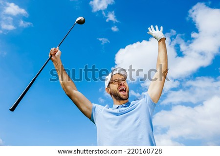 I won! Low angle view of young happy golfer holding driver and raising his arms with blue sky as background - stock photo