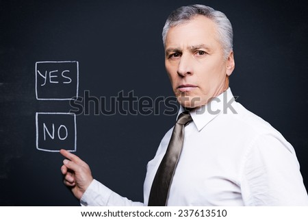 I would say no. Confident senior man in formalwear looking at camera and pointing chalk drawing on blackboard  - stock photo