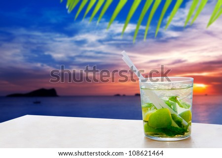 Ibiza cala Conta Conmte sunset with Mojito drink cocktail [ photo-illustration]
