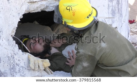 IBTIN, ISRAEL - DECEMBER 17, 2015: Israeli Homeland Security paramedic measures the pulse of earthquake rocket attack tsunami injured soldier buried in the rubble during drill - stock photo