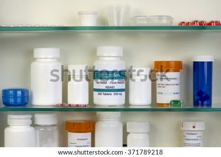 Ibuprofen bottle in medicine cabinet.  Labels are all fictitious. - stock photo