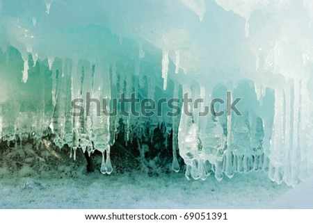 Ice and icicles forming a cave-like structure beautifully illuminated by sunlight. - stock photo
