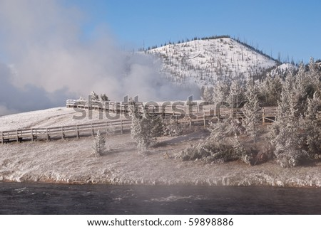 Ice and snow coat the trees and boardwlk at Grand Prismatic Geyser