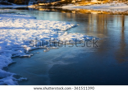 Ice and snow on a frozen lake in a winter sunny day
