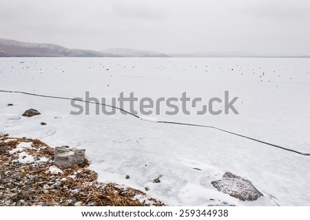 Ice and snow on the lake. Beautiful winter landscape - stock photo