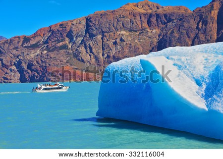 Ice and sun Patagonia, Argentina. Excursion on the tourist boat on Lake Viedma. White and blue huge icebergs floating near the ship broadside - stock photo