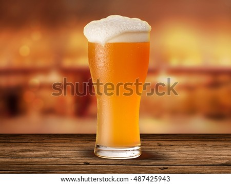 Ice Beer glass on the background of the bar pub, on the wooden table and orange bokeh effect background