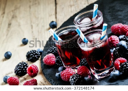 Ice berry tea with raspberries, blackberries and blueberries, selective focus - stock photo