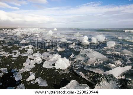 Ice blocks on a black sand beach near Jokulsarlon, Iceland - stock photo