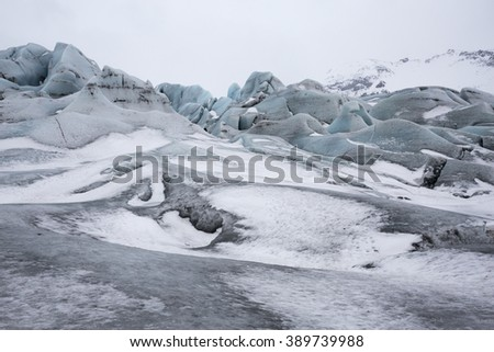 Ice blue colours of Skaftafell Glacial tongue covered in snow in Skaftafell National Park, Iceland - stock photo