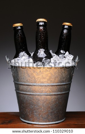 Ice bucket with three brown bottles of beer on a wet wood bar counter top. Vertical format on a light to dark gray background. - stock photo