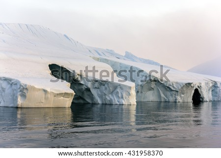 ice caves on arctic ocean at Ilulissat ice fjotd in Greenland - stock photo