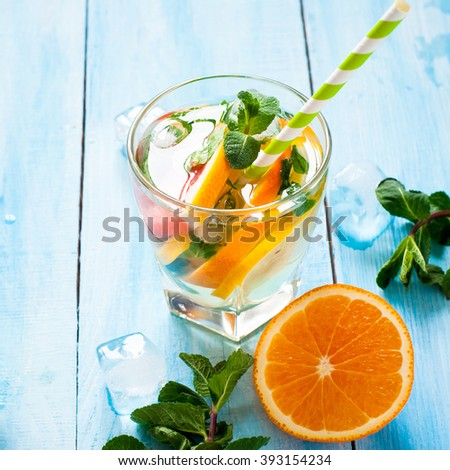 Ice citrus drink with lemon, orange, grapefruit and mint at blue. Copy space. - stock photo