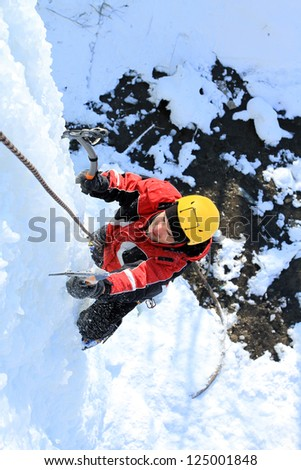 Ice climbing the waterfall. - stock photo