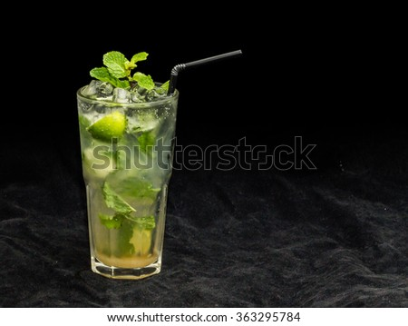 ice  cocktail drink Mojito lime lemon and mint on ice with black background - stock photo