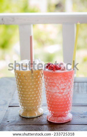 Ice coffee and Strawberry Smoothie on wood table. - stock photo