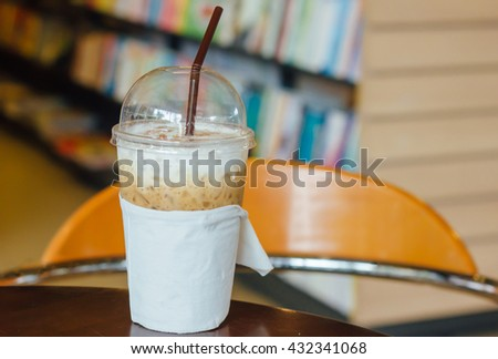 ice coffee concept : plastic glass of ice coffee with blurred book on background on table in cafe shop : food and drink concept