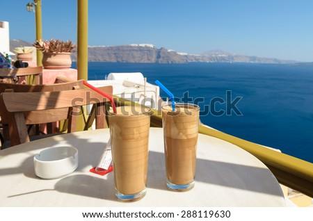 Ice coffee (frape) at balcony view on caldera - stock photo