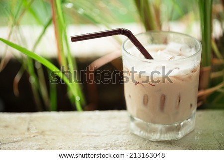 Ice coffee glass on terrace in garden