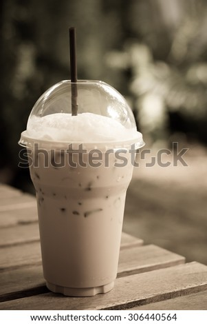 Ice coffee on a wooden table - vintage style effect picture
