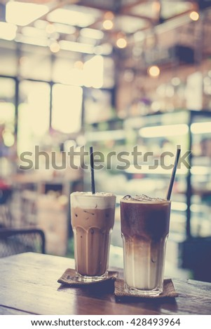 Ice coffee on wood table, vintage style with coffee bar background  - stock photo