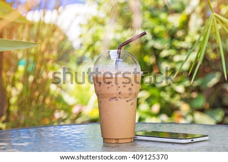 ice coffee to go with smartphone on table in garden - stock photo