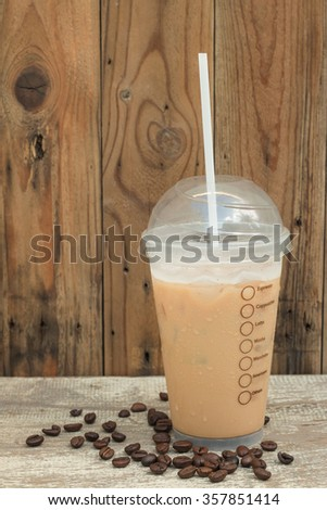 Ice coffee with beans coffee on wood table. for background. - stock photo