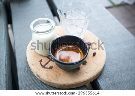 Ice Coffee with milk and ice and coffee seed on wood - stock photo