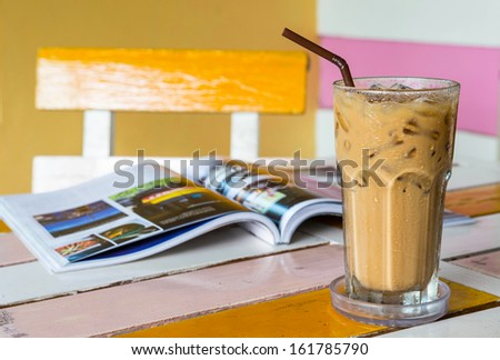 ice coffee with travel journal on table - stock photo