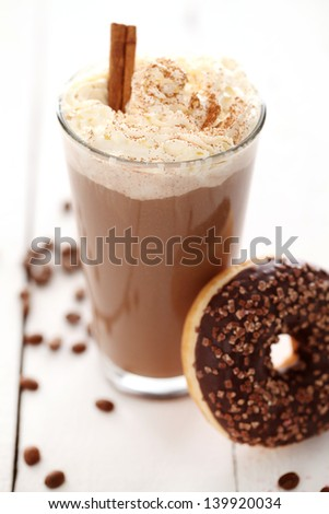 Ice coffee with whipped cream and donut with glaze on a white table - stock photo
