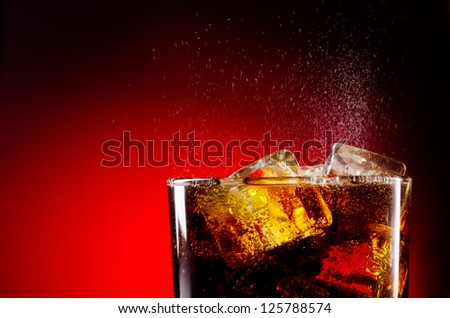 Ice cola with splashing CO bubbles - stock photo