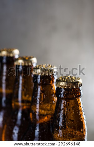 Ice cold beer bottles with drops of dew over the grey background - stock photo
