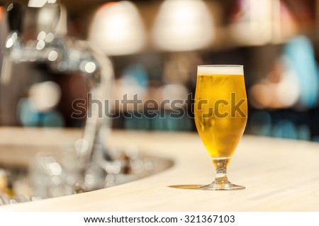 Ice cold beer. Close-up of fresh glass of beer standing on bar counter
