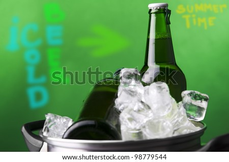 ice cold beer in ice at green background