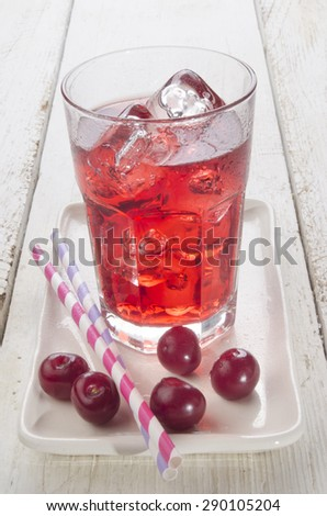 ice cold cherry juice and freshly washed cherries on a plate - stock photo