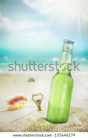 Ice cold green unlabelled bottle of refreshing lager or soda standing upright in the golden sand on a tropical beach under the hot rays of the summer sun - stock photo