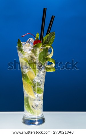 Ice cold mojito cocktail on blue background