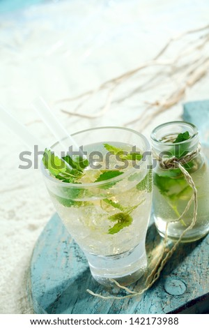 Ice cold mojito cocktail with tangy lime and mint served in a glass with an accompanying carafe - stock photo