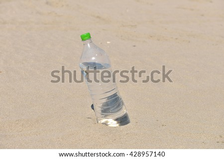 Ice cold unlabelled bottle of refreshing water standing upright in the golden sand on a tropical beach under the hot rays of the summer sun. Water requirements, heat - stock photo