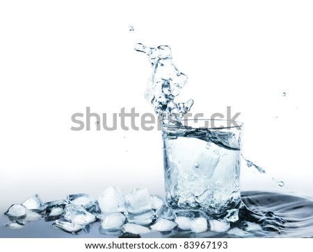 Ice cold water drink in a glass standing in water with ice cubes and water splashing - stock photo