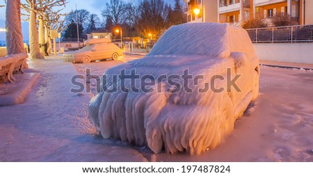 Ice covered car by Lake Geneva at the town of Versoix, Geneva, Switzerland in a winter morning. - stock photo