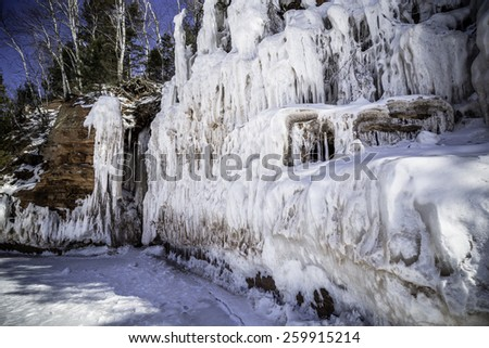 Ice covers the red cliffs along the Superior shore line - stock photo