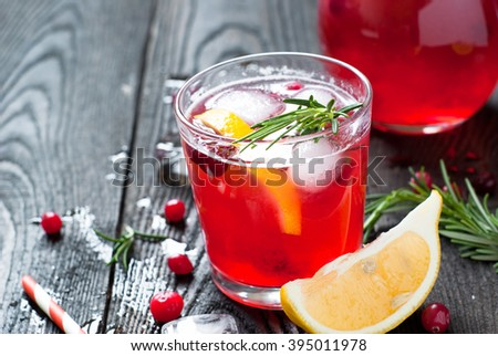 Ice cranberry drink with lemon and rosemary in a glass. - stock photo