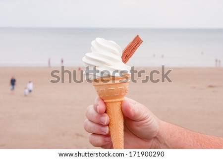 Ice- cream cone with  soft ice cream and chocolate flake with ocean as backdrop  - stock photo