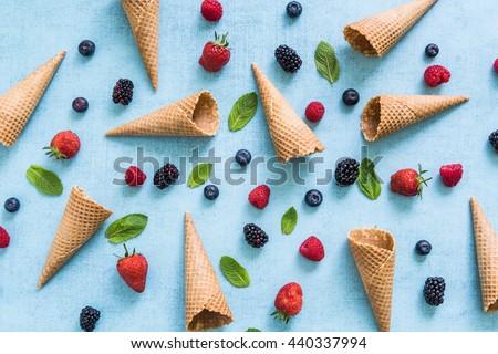 ice cream cones and fresh berries, summer flat lay background - stock photo